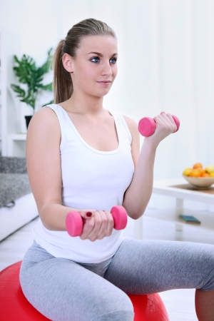woman lifting dumbbells while sitting on a yoga ball photo