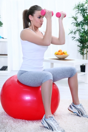 pretty young woman sitting on pilates ball and lifting dumbbells during exercising, breathing correctly Stock Photo - 14734470
