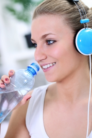 Fitness girl drinking water with headphones photo