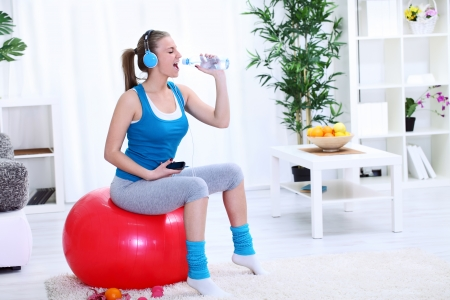 fit ball: Teenager girl singing in bottle, having fun during exercise Stock Photo