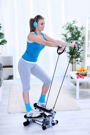 home trainer: Young woman  exercising at home on stepper trainer
