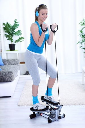 Young woman workout on steeper in living room Stock Photo - 14734592