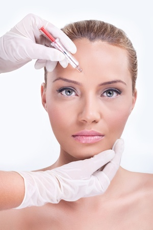 Woman receiving botox injection in the eyebrow zone photo