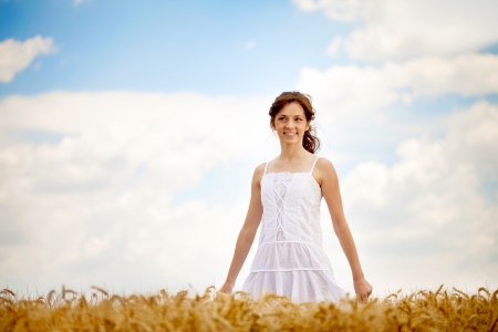 Young smiling woman in white dress in field with wheat photo