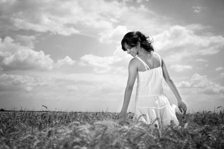 Young woman walking through wheat field touching wheat, black and white photo