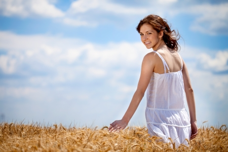 Girl walking thought golden wheat field photo
