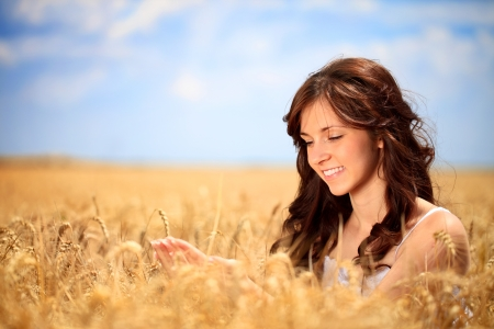Smiling young woman in golden wheat take care of the wheat photo
