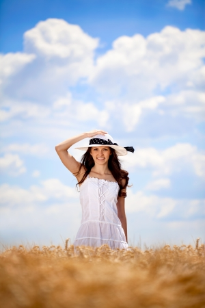 young beautiful woman in golden wheat field photo