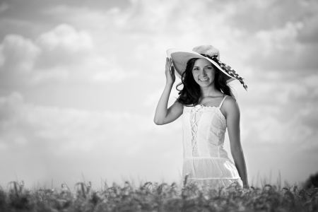 Gorgeous woman with hat enjoying in wheat field photo
