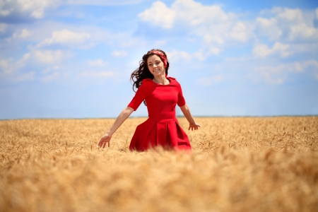beautiful girl in a red dress walking through a wheat field. photo
