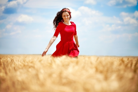 beautiful young, romantic woman running across wheat field photo