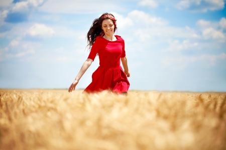 beautiful young, romantic woman running across wheat field photo