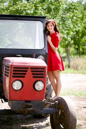girl in red dress:  Beautiful farm girl on tractor