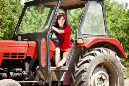 non urban:  Beautiful woman driving tractor