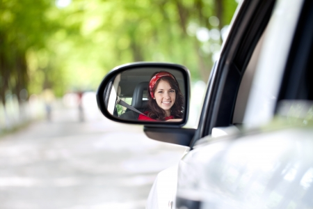 woman driving a car and smiling in the mirror photo