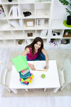smiling teenage girl doing homework in living room  photo