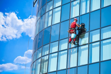 Window washer building windows from outside and reflect the sky in the windows