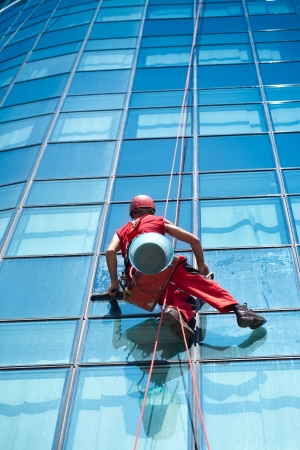 window washer: Washer wash the windows of modern skyscraper, high risk work Stock Photo