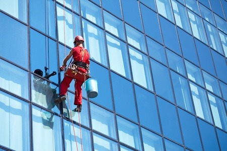window cleaner working on a glass facade modern skyscraper Foto de archivo