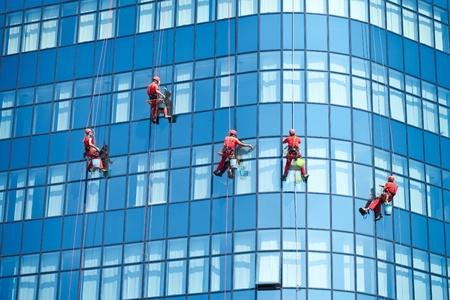 Fünf Arbeiter waschen Fenster im Bürogebäude Standard-Bild - 86751573