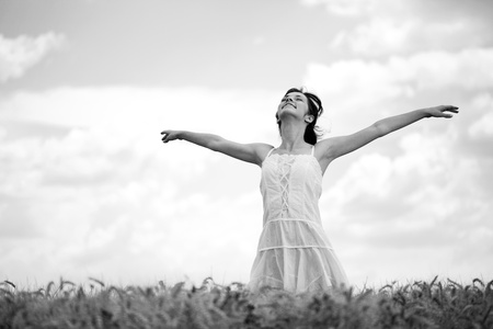 Young woman standing in wheat field, black and white
