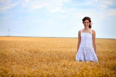 young woman in white dress standing in wheat field photo