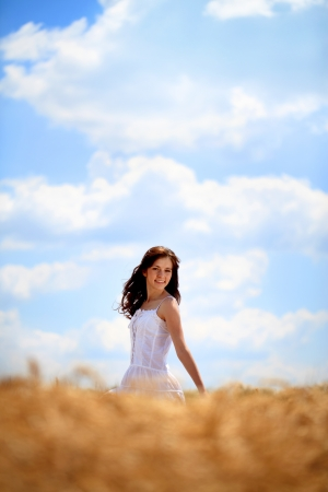Happy young woman enjoying in sun on the wheat field photo