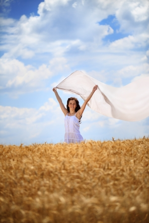 Young woman with white scarf on wind standing in wheat field photo