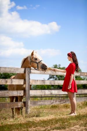 femme et cheval: Jeune fille mignonne avec cheval à la ferme