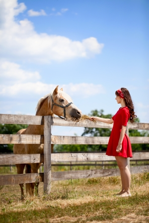 sundress:  Young cute girl  with horse on farm Stock Photo
