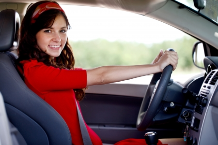 Happy smiling woman driving car, looking at camera