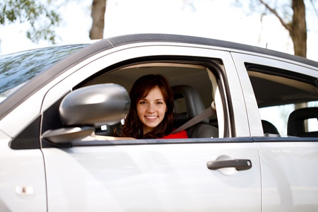 Smiling young woman driving her new, modern car photo