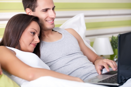 Young man and woman working on laptop in bed photo