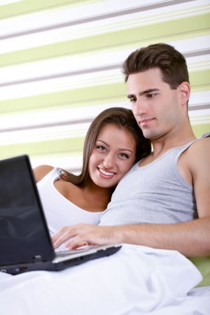 young couple browsing the internet in bed  photo