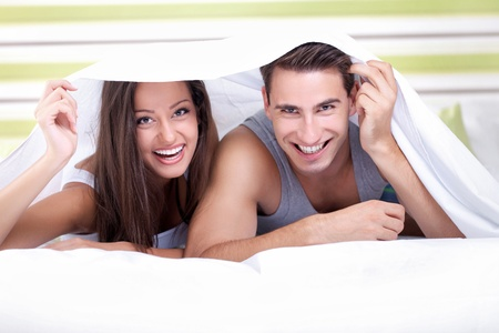 sexy woman on bed: Young couple smiling playing under the sheets in bedroom