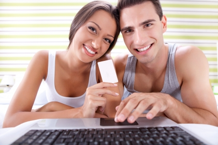 Young smiling couple shopping online, lying in bedroom  photo