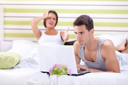 separate:  Problems in bed, woman screaming at man while he works on laptop Stock Photo