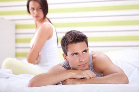 Angry woman looking at man,  problems in bed photo