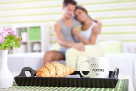 comida rica: buenos días, feliz pareja en la cama con el desayuno en el foco Foto de archivo