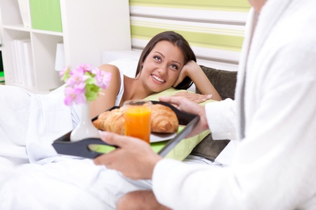 pretty young woman in bed with her boyfriend serving breakfast photo