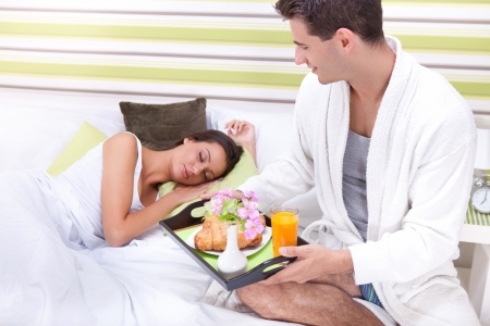 Portrait of happy young man serving breakfast for his girlfriend in bed at home photo