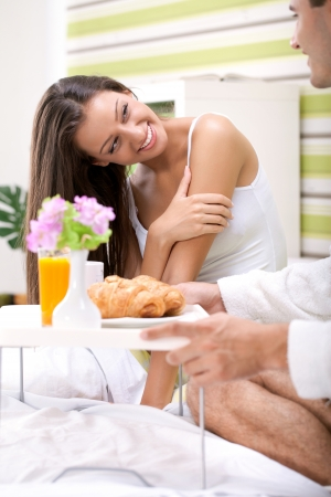 beautiful young woman in bed looking in her husband serving breakfast, thanks for breakfast  photo