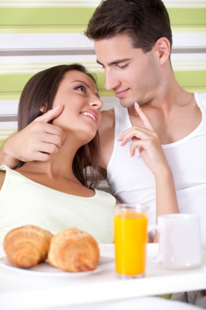 Loving couple having breakfast lying in the bed at home photo