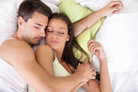 Portrait of lovely young couple sleeping together on bed photo