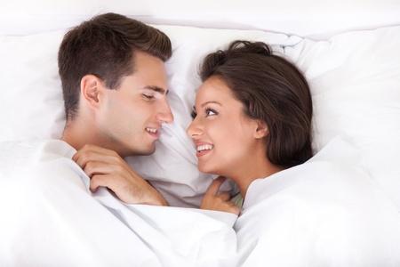 sexualidad: Pareja en la cama sonriendo el uno al otro Foto de archivo