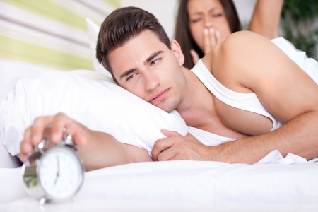 snoozing: Young snoozing couple in bed waking up to alarm clock.
