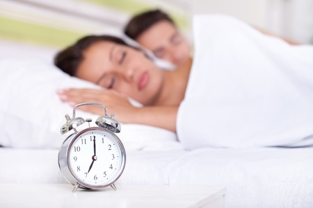 Young couple sleeping together in bed with  alarm clock photo