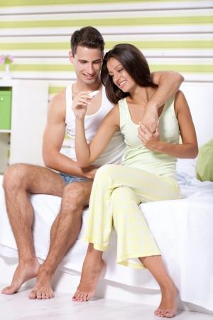 prueba de embarazo: Pareja alegre averiguar los resultados de una prueba de embarazo en el dormitorio