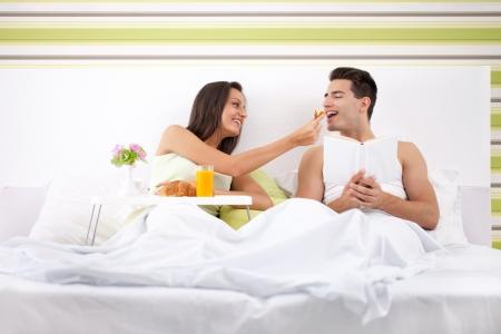 pareja en la cama: hermosa pareja de desayunar en la cama, muchacha llenando su novio