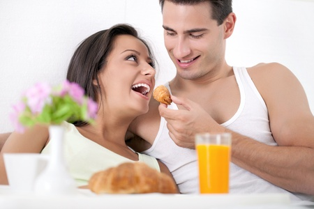 Beautiful smiling young couple having breakfast in bed, morning in bed  photo